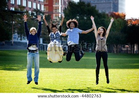 A group of happy people running towads the camera.  Sharp focus on rear three people, motion blur on front person. - stock photo