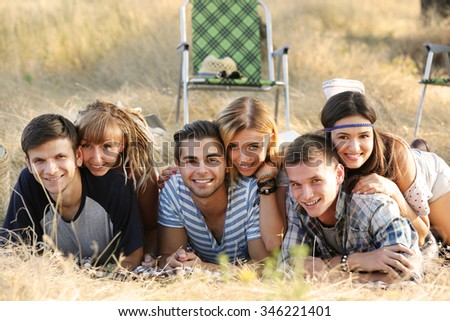A group of happy smiling friends lying in the grass outdoors - stock photo