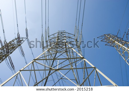 a group of high voltage power towers and electrical lines going over a hill from the power station