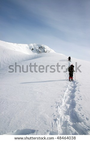 A group of hikers arrived the pass towards the snow peak during snowshoeing near BC, Canada. - stock photo