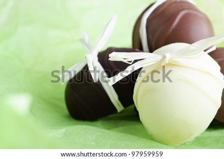 A group of home made Easter egg chocolates, bow tied with raffia ribbon, nestling on a fresh, light Spring green background.  Copy space to left. - stock photo