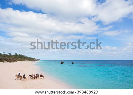 a group of horseback riders on the beach in Bermuda - stock photo