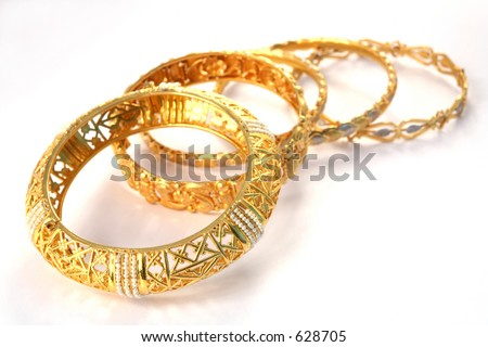 A group of 22k gold bracelets, showing details of the workmanship. The one at the front is inlaid with small Gulf pearls. The style is Arabian or Indian/Eastern.