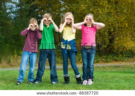 A group of kids making binoculars with their hands outside. - stock photo