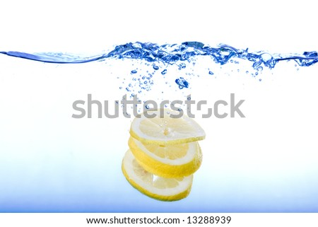 A group of lemon slices dropped in water with bubbles