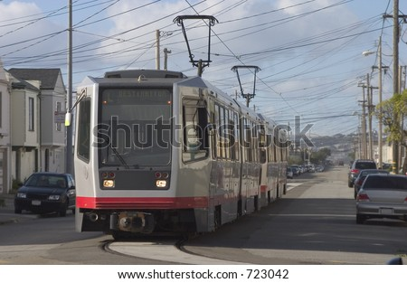 A group of light rail cars makes their way through San Francisco's  Outer Sunset neighborhood.