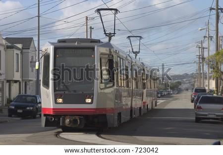 A group of light rail cars makes their way through San Francisco's  Outer Sunset neighborhood. - stock photo