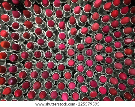 A group of many different shades of red lipstick. - stock photo