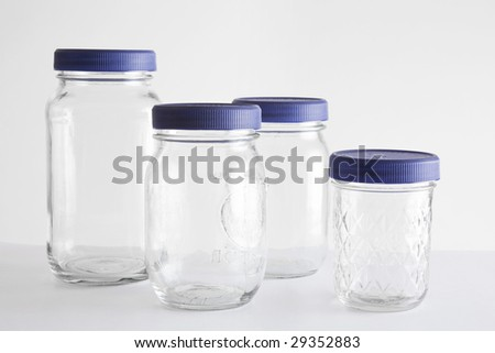 A group of mason (canning) jars that have been re-purposed with blue lids to store small items. - stock photo