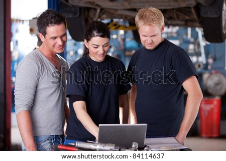 A group of mechanics referring to a laptop for service order or diagnostics results - stock photo