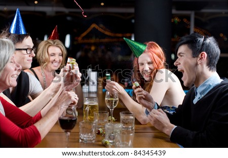 A group of men and women of mixed ages, wearing party hats and popping streamers. - stock photo