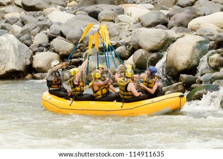 A group of men and women, with a guide, white water rafting on the Pastaza river, Ecuador - stock photo