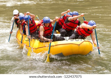 A GROUP OF MEN AND WOMEN, WITH A GUIDE, WHITEWATER RAFTING ON THE PATATE RIVER, ECUADOR  - stock photo