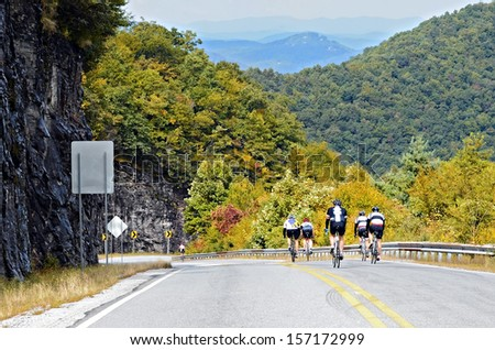 A group of men riding down a mountain with fall colors beginning to show. - stock photo