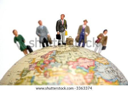 A group of miniature businessmen and businesswomen standing on a globe. Focus is on the man in the center with the others out of focus. - stock photo