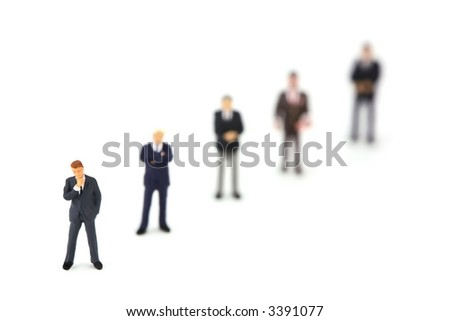A group of miniature businessmen standing in a row diagonally. Focus in on the man in the bottom left corner. The rest of out of focus due to shallow depth of field. Leadership concept. - stock photo
