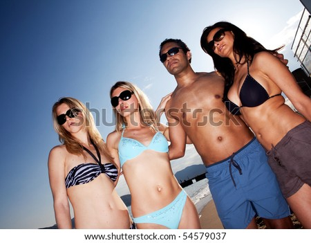 A group of models on the beach against a blue sky - stock photo