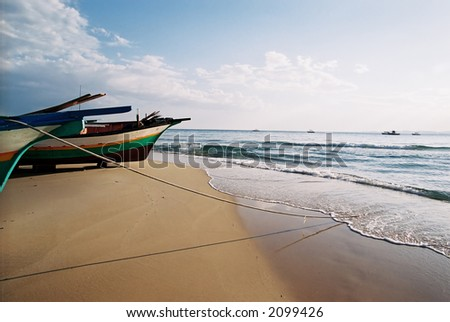 A group of moored fishing boats along the sandy beach in Tunisia.