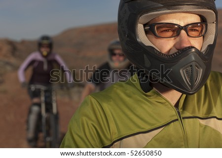 A group of mountain bikers is wearing protective eyewear and a helmets in a desert setting. Horizontal shot. - stock photo