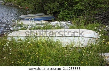 A group of old row boats by the water's edge. - stock photo