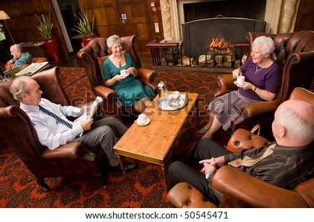 A group of older senior friends enjoying tea and talking in hotel lounge area - stock photo