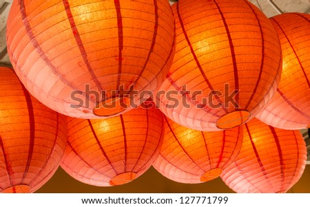 A group of orange paper lanterns hanging from the ceiling - stock photo
