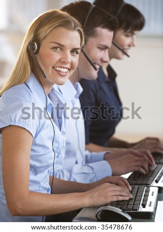 A group of people are typing on keyboards and wearing headsets.  The young woman is smiling at the camera.  Vertically framed shot. - stock photo