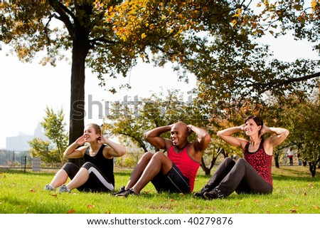 A group of people doing exercises in the park - stock photo