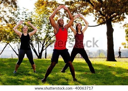 A group of people doing jumping jacks in the park - stock photo