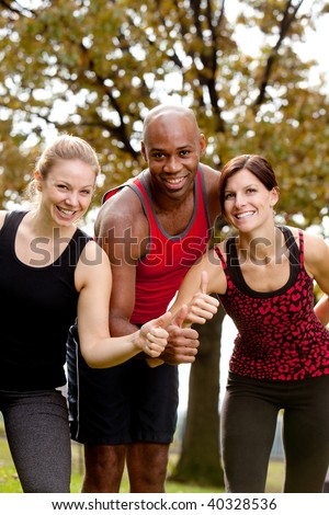 A group of people exercising in the park, giving a thumbs up to the camera - stock photo