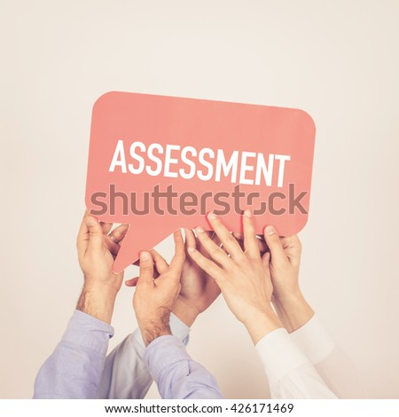 A group of people holding the Assessment written speech bubble - stock photo