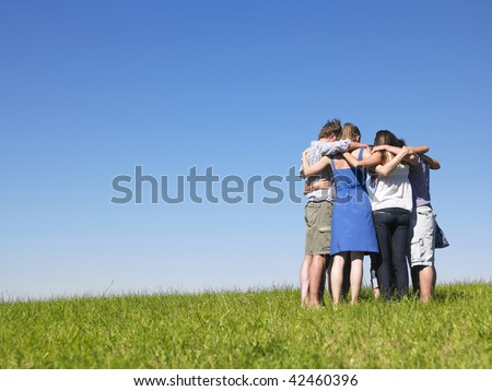 A group of people huddle in a field. Horizontally framed shot. - stock photo