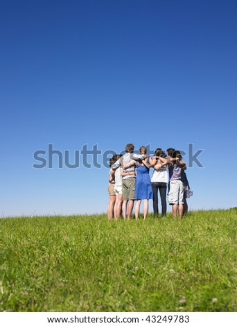 A group of people huddle in a field. Vertically framed shot. - stock photo