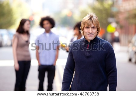 A group of people in a city setting - a caucasian male in the foreground - stock photo