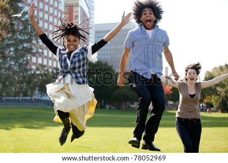 A group of people jumping for joy in a city park - stock photo