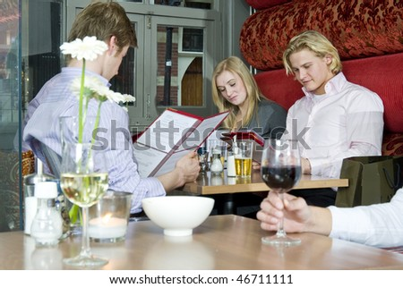 A group of people looking at the menu in a restaurant - stock photo