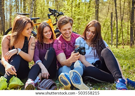 A group of people looking photo pictures on compact cameras and relaxing after bicycle ride in a forest.