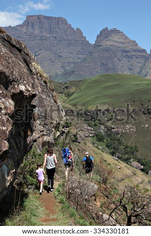 A group of people make their way along a narrow hiking trail on the side of a mountain in the Drakensberg mountain range in rural KwaZulu-Natal, South Africa.