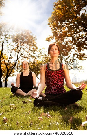 A group of people meditating in a city park - stock photo