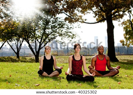 A group of people meditation in a city park - stock photo