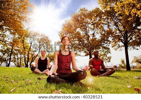 A group of people meditation in a city park in the morning - taken into the sun with lens flare - stock photo