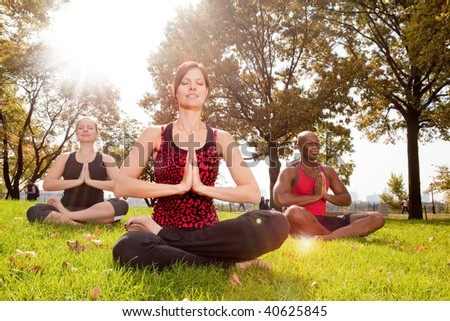 A group of people meditation in the park - taken into the sun with lens flare - stock photo
