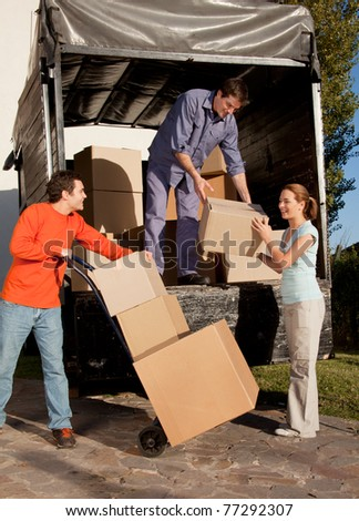 A group of people moving boxes from a trailer - stock photo