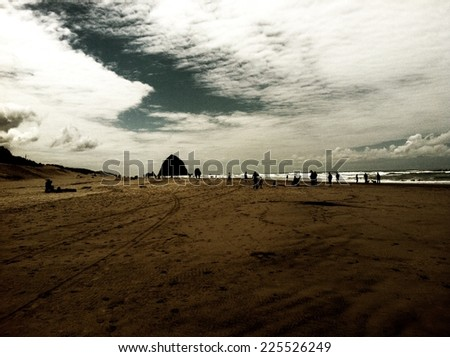 A group of people on a beach under white clouds. - stock photo