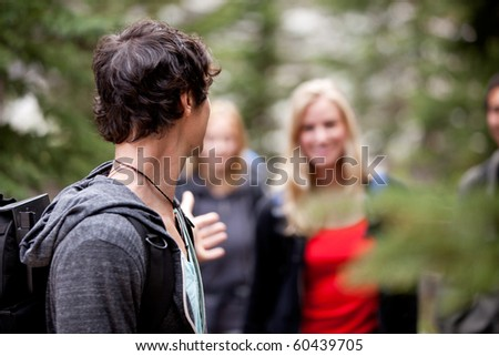 A group of people on a hike, a man waiting for a girl