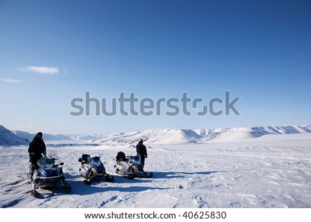 A group of people on a snowmobile trip in a winter landscape