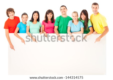 A group of people pointing down at a blank surface.