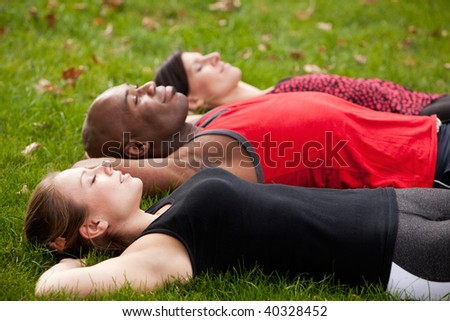 A group of people relaxing in a park after exercise - stock photo