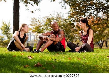 A group of people relaxing in the park after exercise - stock photo