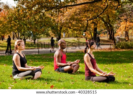A group of people relaxing with meditation in a city park - stock photo